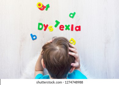 A school aged boy holding his head in hands in frustration because of dyslexia failing to read magnetic letters shot from above horizontal.