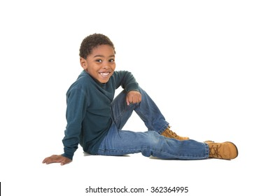 A school aged boy sitting on the floor isolated on white