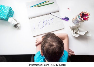 School aged boy sitting at the table, frustrated, helpless and sad with himself and his writing because of dysgraphia, shot from above, horizontal position.