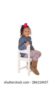 A school aged child sitting on a chair