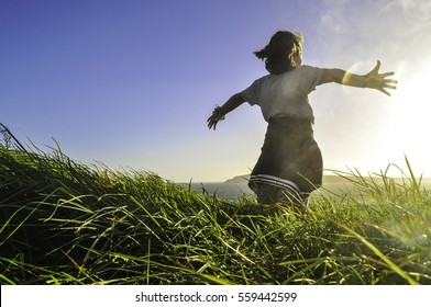 School aged child stands in long grass with arms outstretched atop a  hill facing towards a golden sunset over the ocean