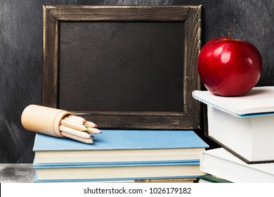 School attributes - black board, books, colored pencils, notebook, apple on dark background. Copy space