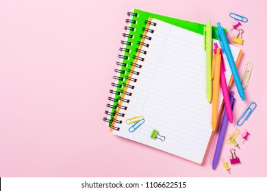 School background with notebooks and colorful study supplies over pink. Back to school concept with copy space for text.
