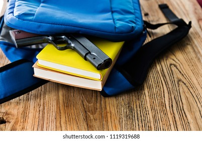 School backpack with books and gun on desk.
