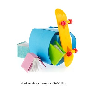 School backpack, books of origami and skate board, isolated on white background.