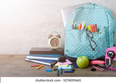 School backpack with coloured pencil and school supplies on brown wood table background. Back to school concept.