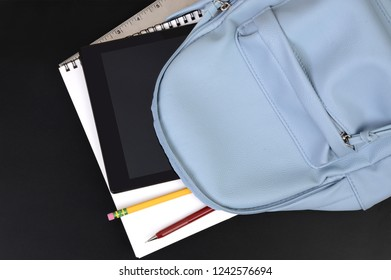 School backpack with pencils ,tablet and books on blackboard background