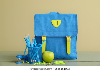 School backpack and stationery on table