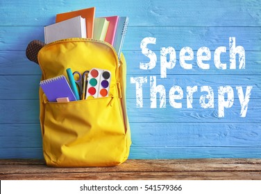School backpack with stationery and text SPEECH THERAPY on blue wooden background