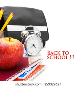 School bag, an alarm clock and other school accessories on a white background.