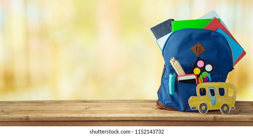 School bag backpack with notebooks, smart phone, pencils and school bus on wooden table.