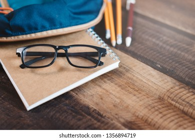 school bag, notebook,pencil,pen and eyeglasses on a wooden table.concept of school equipment and education. Selective focus on eyeglasses