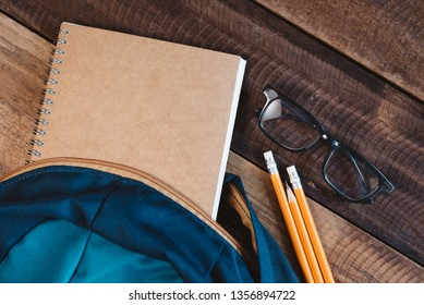 school bag, notebook,pencil,pen and eyeglasses on a wooden table.concept of school equipment and education