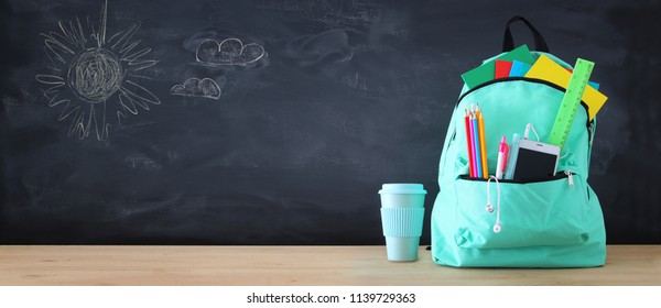 school bag with stationery and notebooks in front of blackboard. Back to school concept