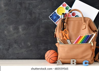 school bag and stuff on cork blackboard background with copy space, study education concept