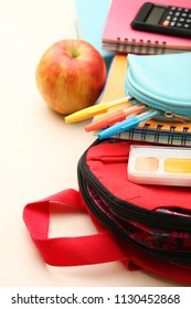 The school bag with school supplies lies on a neutral background.