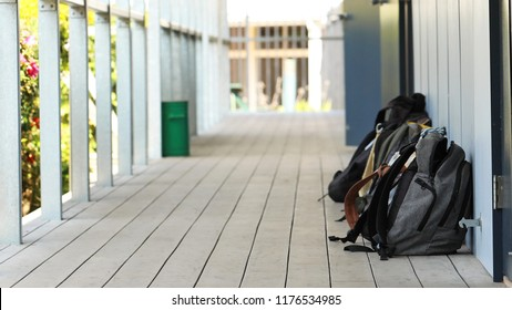 school bags outside a classroom at high school. Long narrow hallway or outdoor corridor with bright sunshine. Educational theme concept. Backpacks in the school yard. Back to school, bullying, anxiety