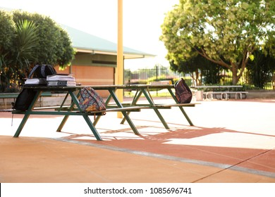 school bags sitting on a table in the school yard. no students. nice day, long shadows. notes folders and exam revision material for high school students. education concept