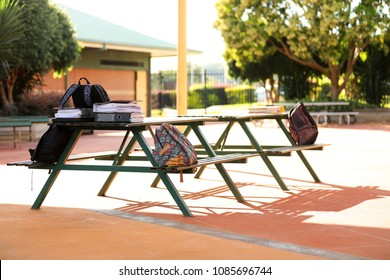 school bags sitting on a table in the school yard. no students. nice day, long shadows. notes folders and exam revision material for high school students. education concept. Back to school