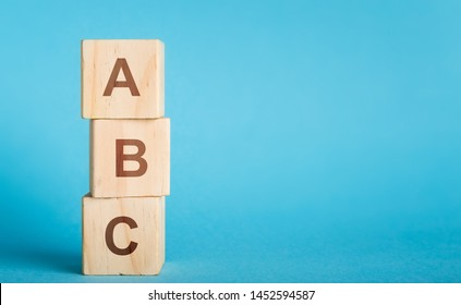 School begginnings. ABC letters of wooden blocks in pillar form on blue background, copy space
