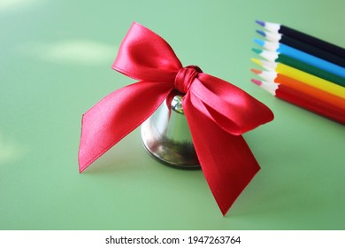 School bell with a red bow close-up. Colored pencils rainbow colors are arranged in a row on a green background. Back to school.