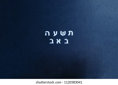 School black chalkboard with text Tisha B'Av written in hebrew. Tisha B'Av day in Judaism, on which a number of disasters in Jewish history occurred.
