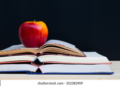 school books and apple against blackboard