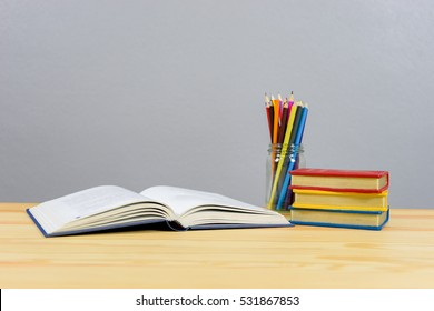 School books ,color pencil ,pen on desk,can creative infographics blackboard inside , the education concept, and gray color background