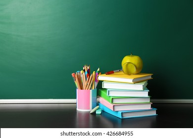School books on desk near chalkboard