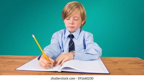 School boy doing homework at desk against green background