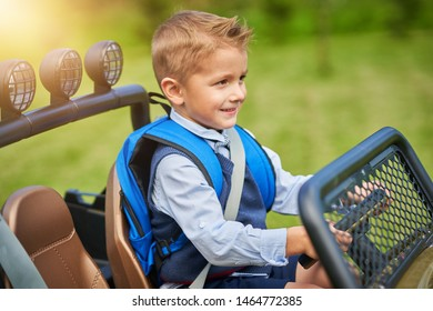 School boy driving kids car with backpack