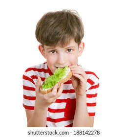 a school boy eats a sandwich with lettuce