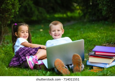 school boy and girl in park watching laptop