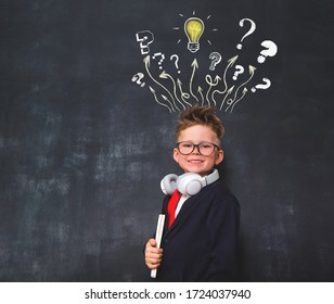 School boy in glasses with light bulb and questions drawn on chalkboard. Education concept