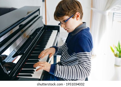 School boy with glasses playing piano in living room. Child having fun with learning to play music instrument. Talented kid during homeschooling corona virus lockdown.