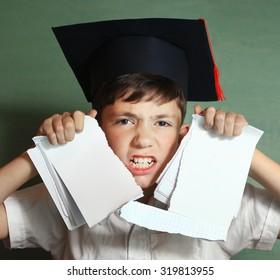 school boy in graduation cap rebel against hard learning
