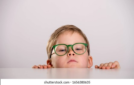 School boy in green eyeglasses. Funny child hiding behind the table