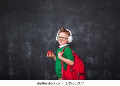 School boy in headphones with red bag and apple in hand against blackboard.