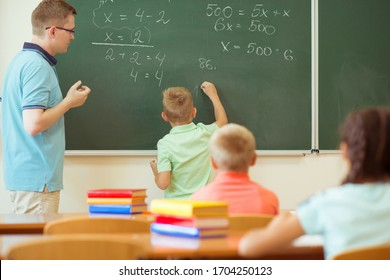 School boy with his teacher at the blackboard solving at math lesson in classroom at school