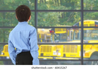 School boy looking out window at buses in parking lot.