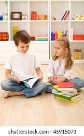 School boy reading to his little preschool sister sitting on the floor