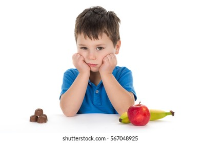 School boy sitting in front of a hard choice - chocolate or fruits.