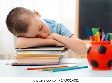 school boy sitting at home classroom lying desk filled with books training material schoolchild sleeping lazy bored to study lack energy fatigue during learning concept Indulge and grimace. overwork