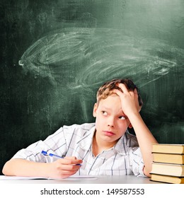 school boy is sitting at table and thinking with chalk board behind him