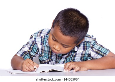 School boy sitting and writing in notebook over white background