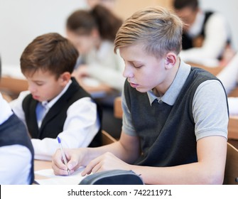 school boy struggling to finish test in class. Diligent student sitting at desk, classroom