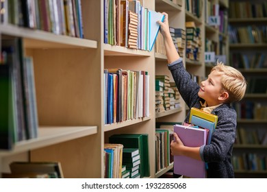 school boy taking books from shelves in library, with a stack of books in hands. child brain development, learn to read, cognitive skills concept