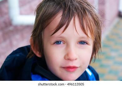 School boy is walking in the rain - outdoor portrait