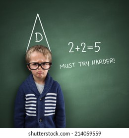School boy wearing a dunce cap against a blackboard with incorrect sums and must try harder note