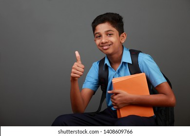 School boy wearing uniform shows thumbs up